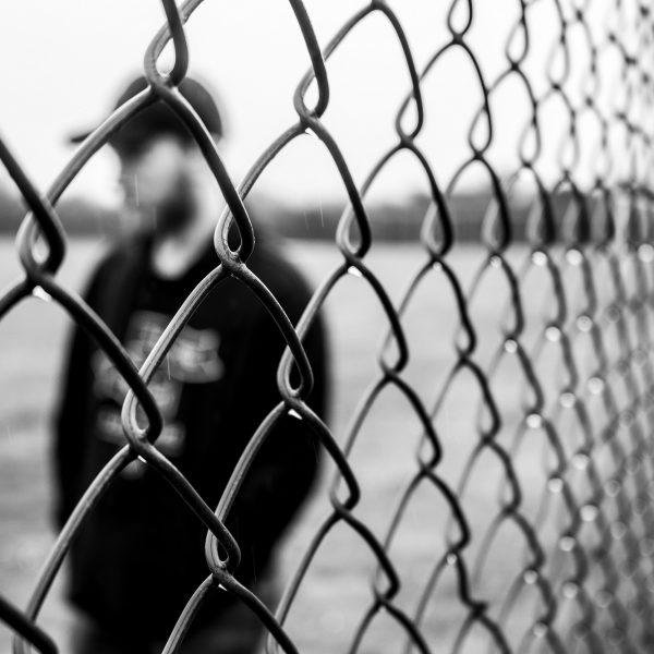 Uomo dietro una grata | © Jake Oates