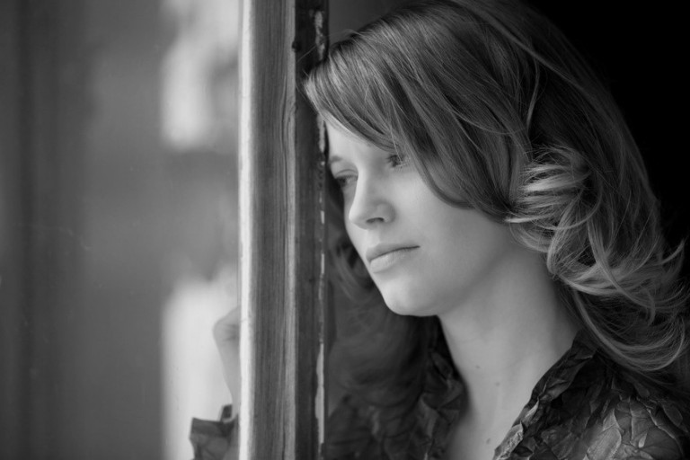 Donna guarda fuori dalla finestra | © redhorst