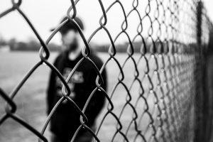 Uomo dietro una grata   © Jake Oates